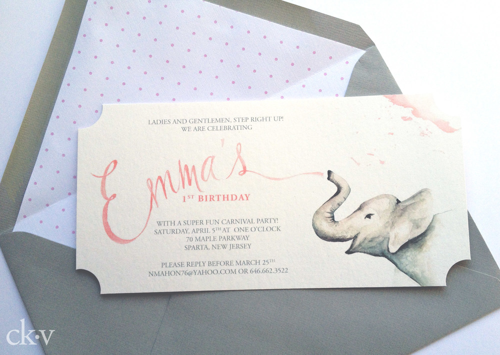 Grey envelope with pink swiss dot liner, ticket shaped invitation on bamboo card.