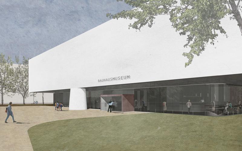 """Ein großes, rechteckiges Gefäß, auf vier kräftigen Pfeilern im Dessauer Stadtpark abgestellt: das neue Bauhausmuseum. Der über 2.100m2 große Ausstellungsbereich, in dem die Schätze des """"Kosmos Bauhaus"""" gezeigt und erklärt werden, ist von der Umgebung vollkommen abgeschottet: Hier stehen die Geschichte und Werke des Bauhaus im Mittelpunkt des Geschehens. >>>>"""