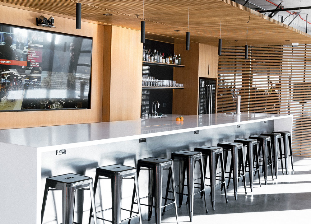BAR AND MULTIMEDIA - A bar style break area for impromptu meetings and entertaining clients/guests. Large multimedia display to showcase projects, hold project unveilings, or large meetings. Full bar, beer taps. Behind, great city views to the west, with garage doors opening up for fresh air.