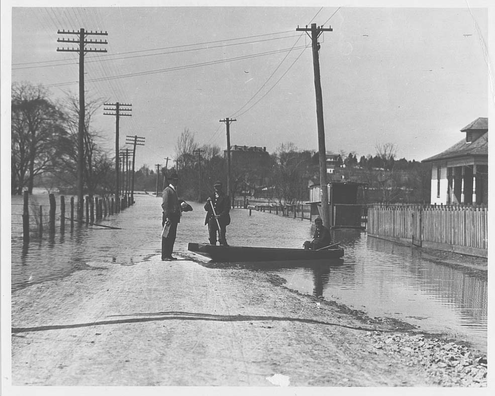 """Nashville Flood of 1926. Street scene showing two men in a skiff talking to a man standing on dry land."""