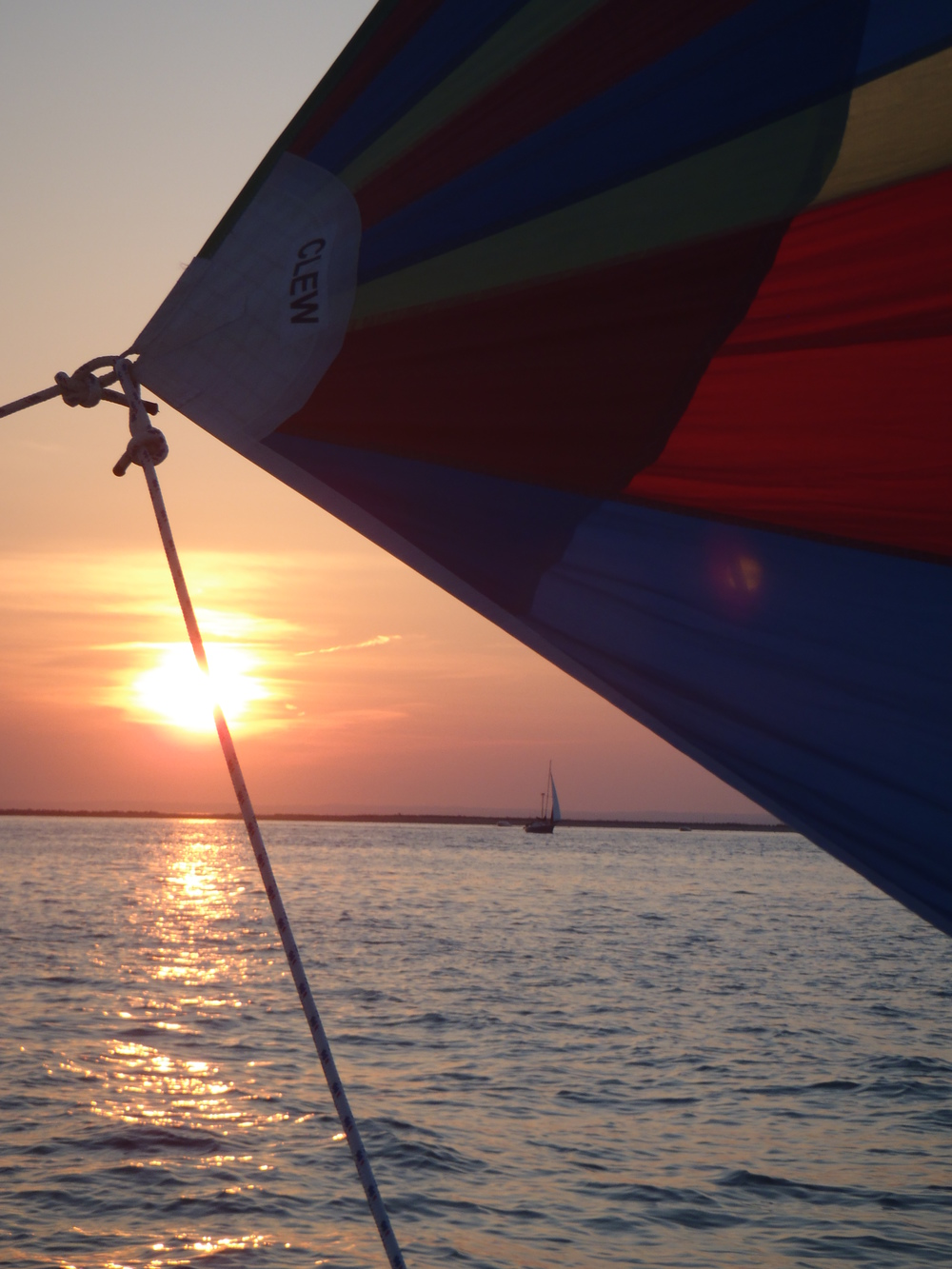 The Asymmetrical Spinnaker's Clew caught with the setting sun on the placid waters of Northport Harbor.