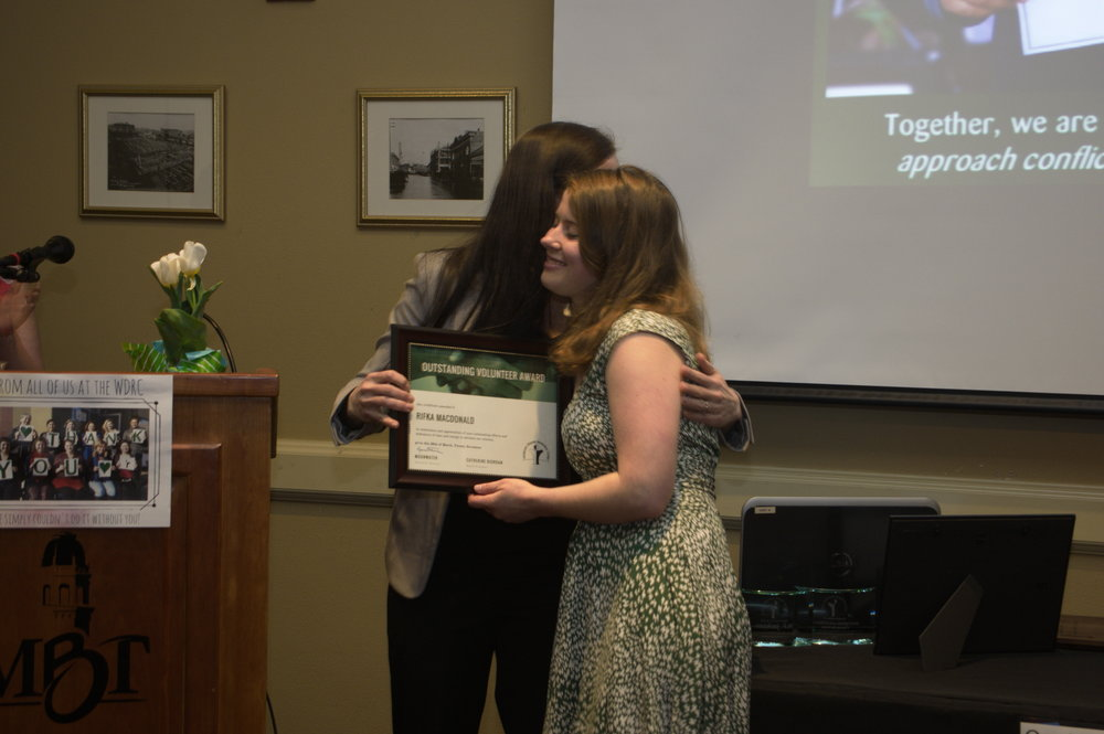 Rifka accepts an award and hug from WDRC Executive Director Moonwater. Photo by  Bellingham Photographer  Phil Rose.