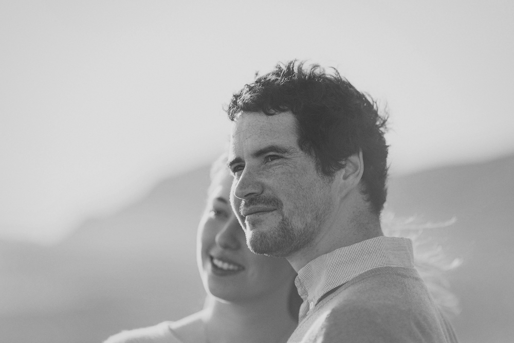 Couple looks out to sea views, with man in focus. Black and white image by Jenny Siaosi.