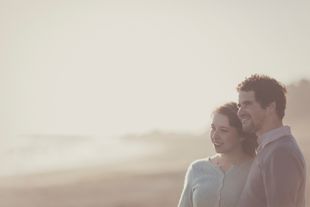 Couple looking out to sea views, rugged landscape. Engagement photography by Jenny Siaosi.