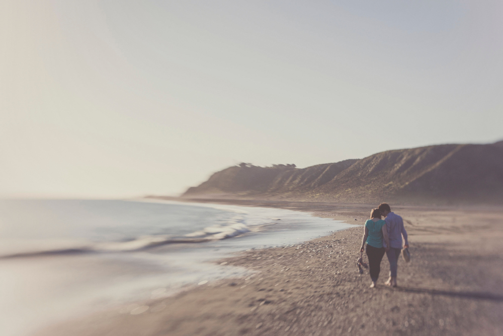Intimate moment between husband and wife walking on rugged beach landscape.