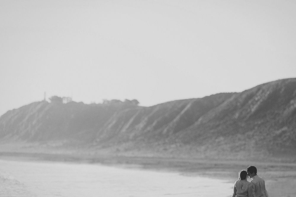 Rugged beach scene of couple enjoying a little moment while walking along beach.