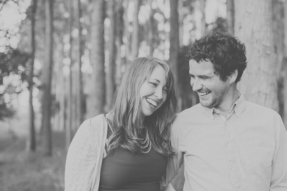 Couple laughing together with trees in background. Photography by Jenny Siaosi.