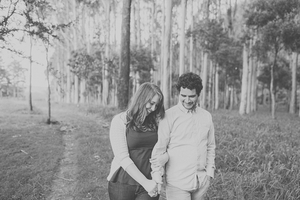 Couple laughing  and walking together with trees in background. Photography by Jenny Siaosi.