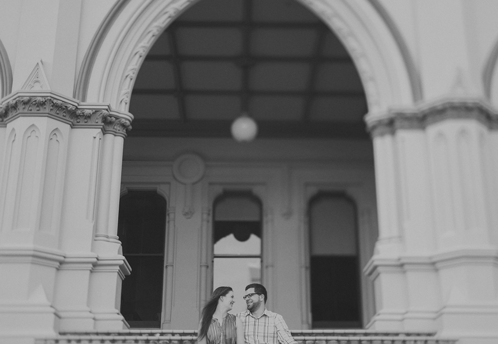 Laughter and a sweet moment shared on an engagement photo shoot in front of parliamentary library in Wellington. Photo by Jenny Siaosi.