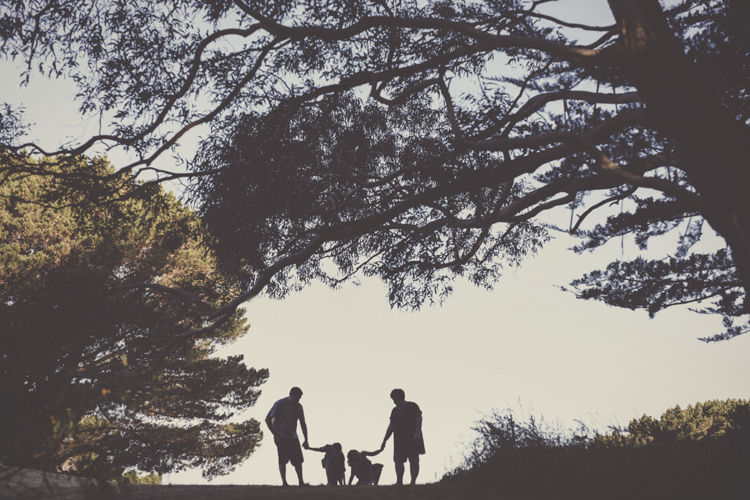 Natural silhouette photo of family, playing amongst the trees. Photo by Siaosi Photography.
