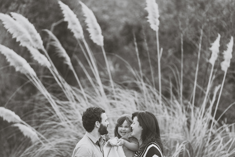 Natural family photograph with toddler laughing and cuddling mum. Toi-toi bush in back ground. Black and white photo by Jenny Siaosi.