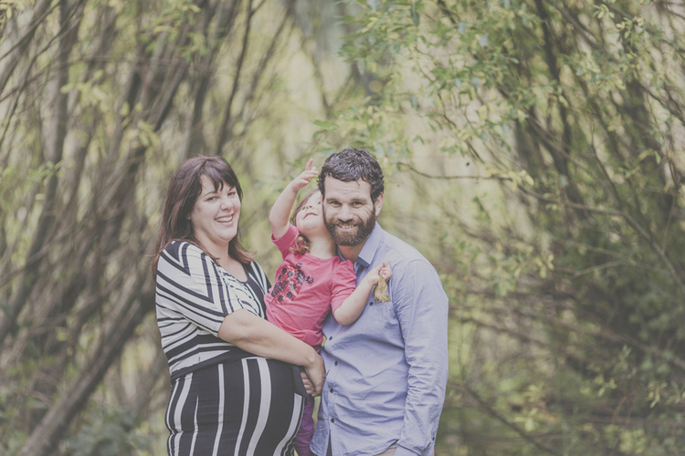 Natural family photograph with toddler hugging dad's shoulders and Mum is expecting. Photo by Jenny Siaosi.