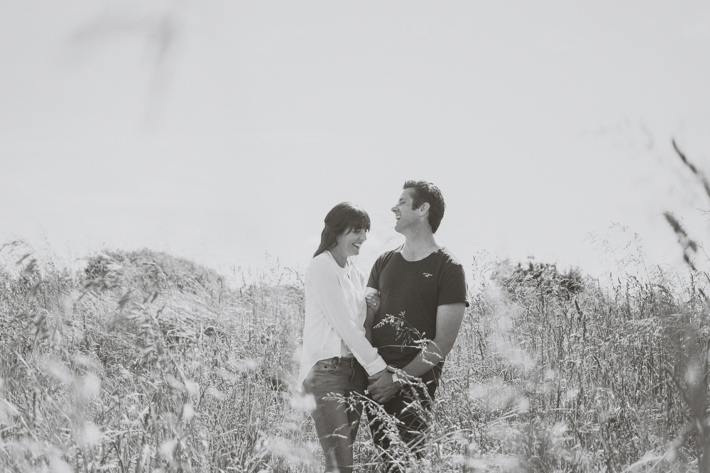 Lovers in long grasses laughing together. Black ad white. Engagement session on beach in Kapiti, NZ.