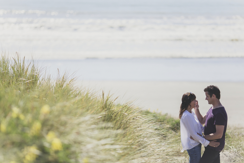 Lovers in sand dune share a moment.  Engagement session on beach in Kapiti, NZ.