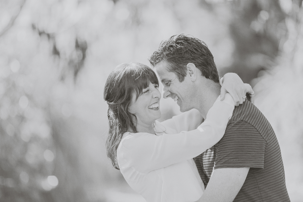Engaged couple embrace, and laugh together. Black and white. Engagement session in Kapiti, NZ. Photography by Jenny Siaosi.