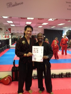 Master Q presents Master Douglas with his Kukkiwon 5th Dan certificate.