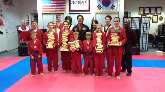 Jack, Donovan, Brady, Briley, and Chris hold their broken boards after successfully testing for their 1st Dan Black Belts.