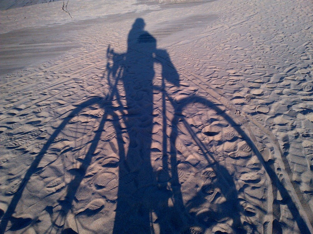 My bike shadow in Sandy-tossed sand