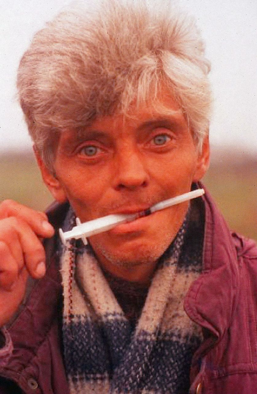 Drug user holds his syringe in his mouth.