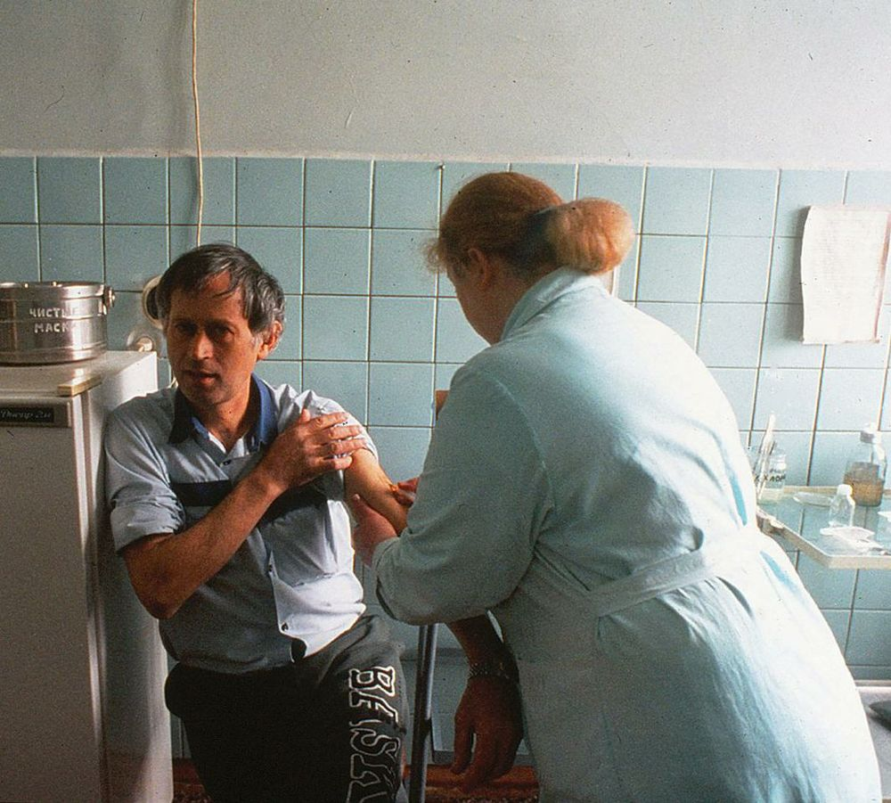 Remarkably, a nurse working on an AIDS ward in Kyiv, Ukraine, draws blood from an HIV+ patient without wearing protective gloves.