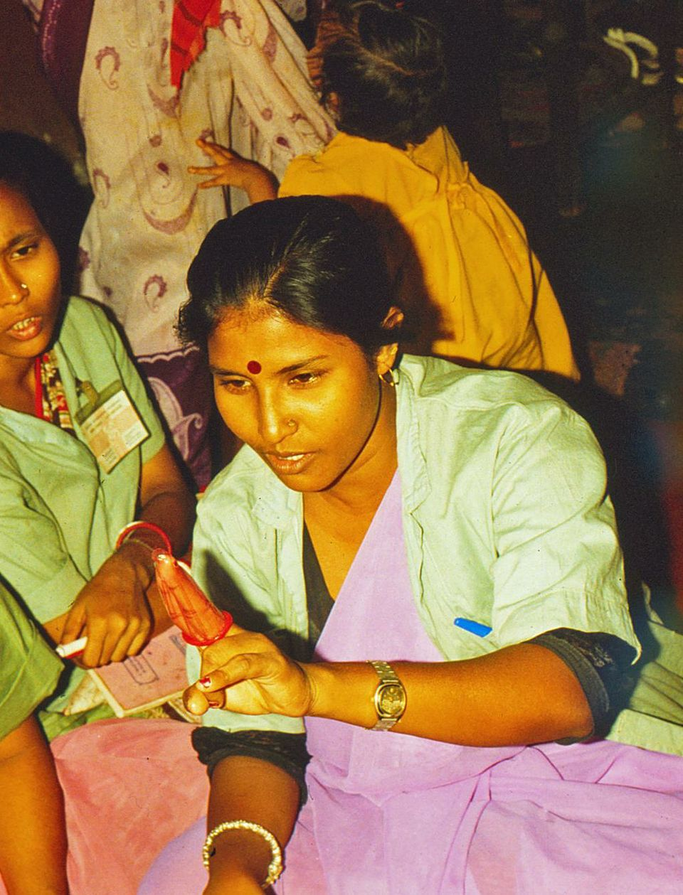 Sex workers in Bombay learn how to use condoms to prevent HIV infection.