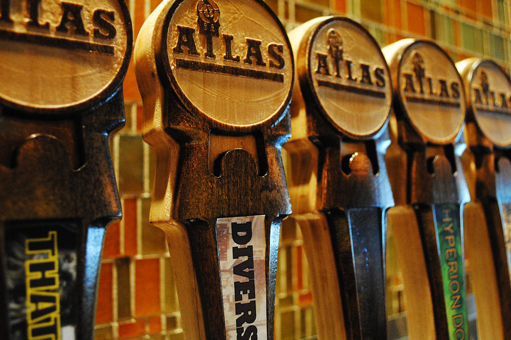 Newly milled tap handles adorn the beautiful bar setup at Atlas.