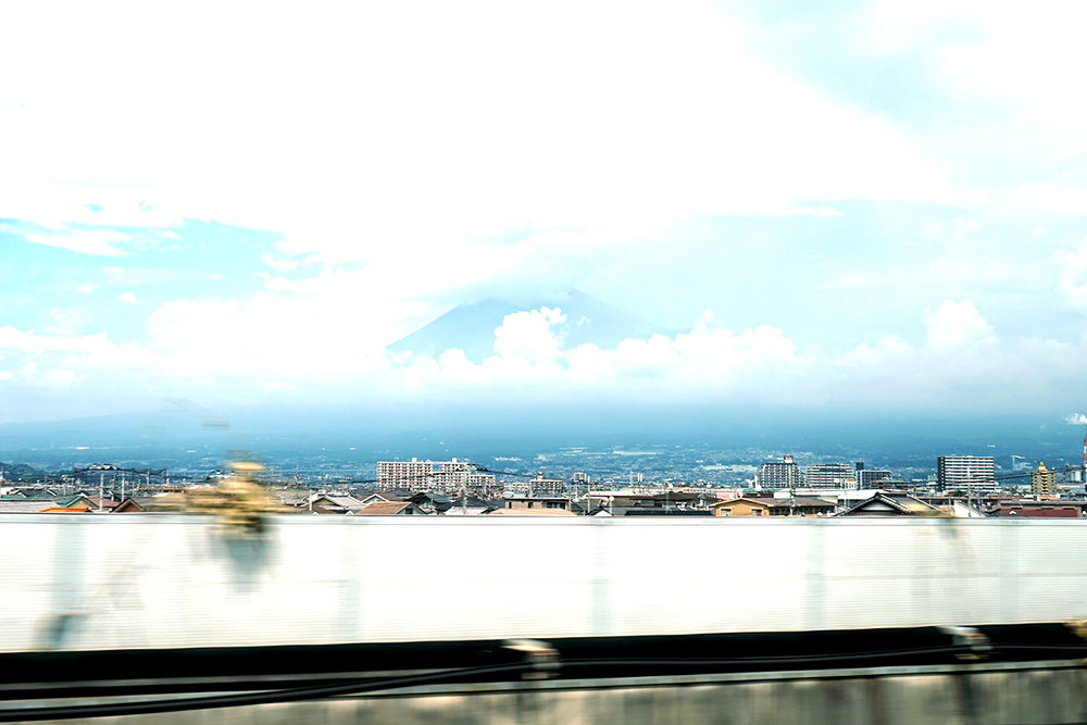 Mt. Fuji peeks out among the clouds, viewable from bustling Tokyo.