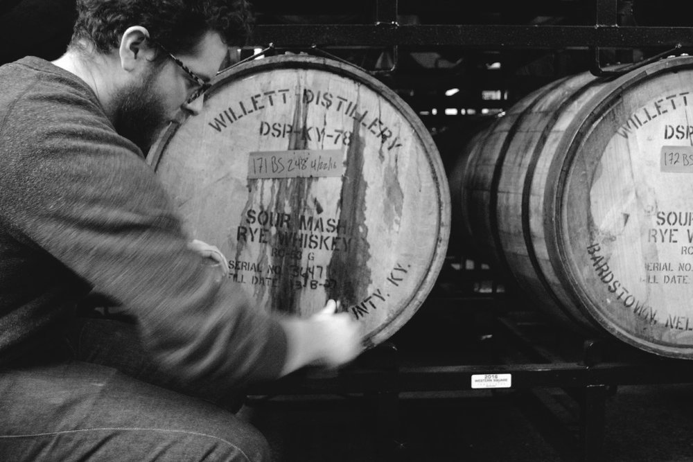 Mike Schallau taps a sample of Bourbon-aged  The Abduction  from the barrel.