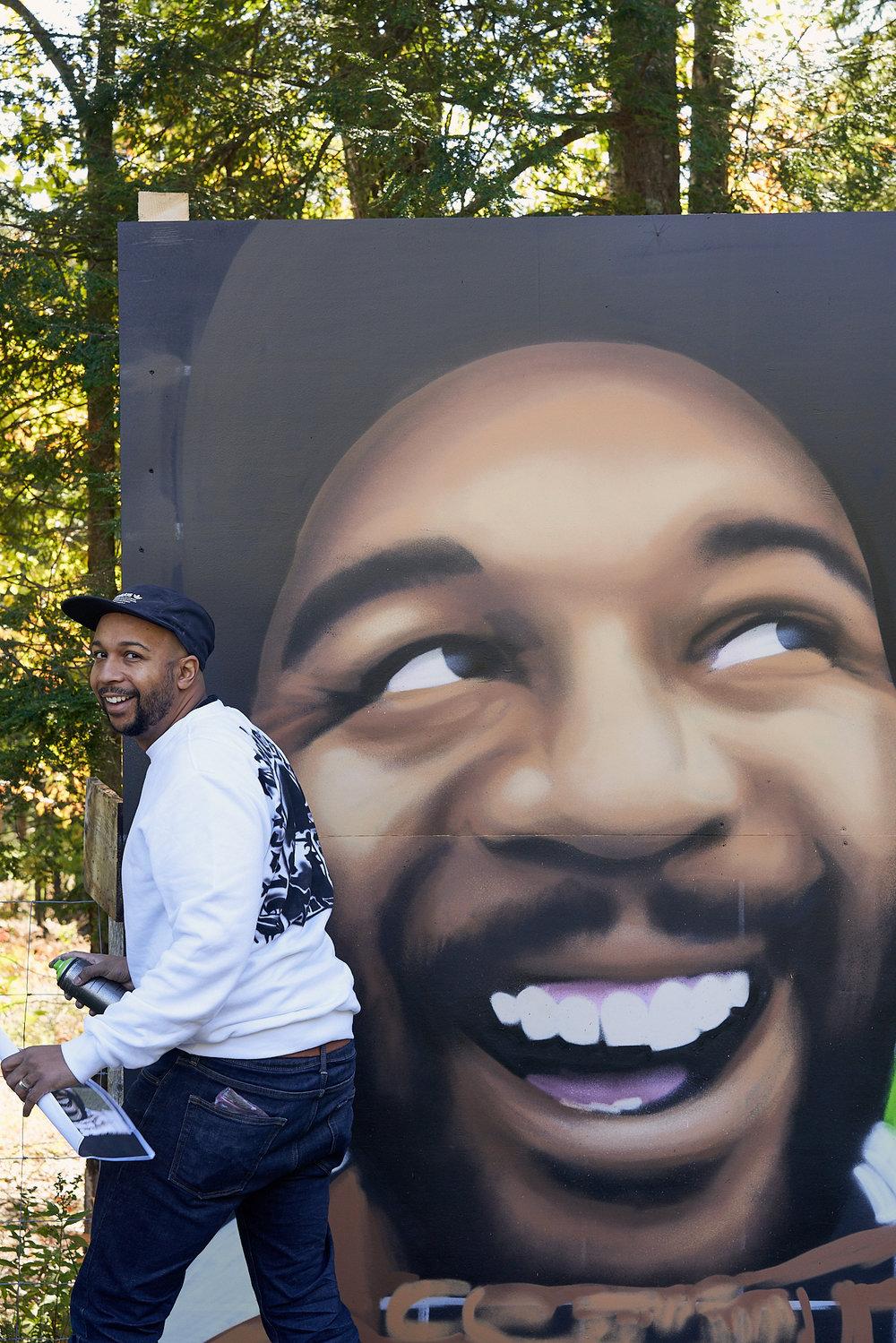 Artist    Ryan Woods    spray paints a self-portrait mural.