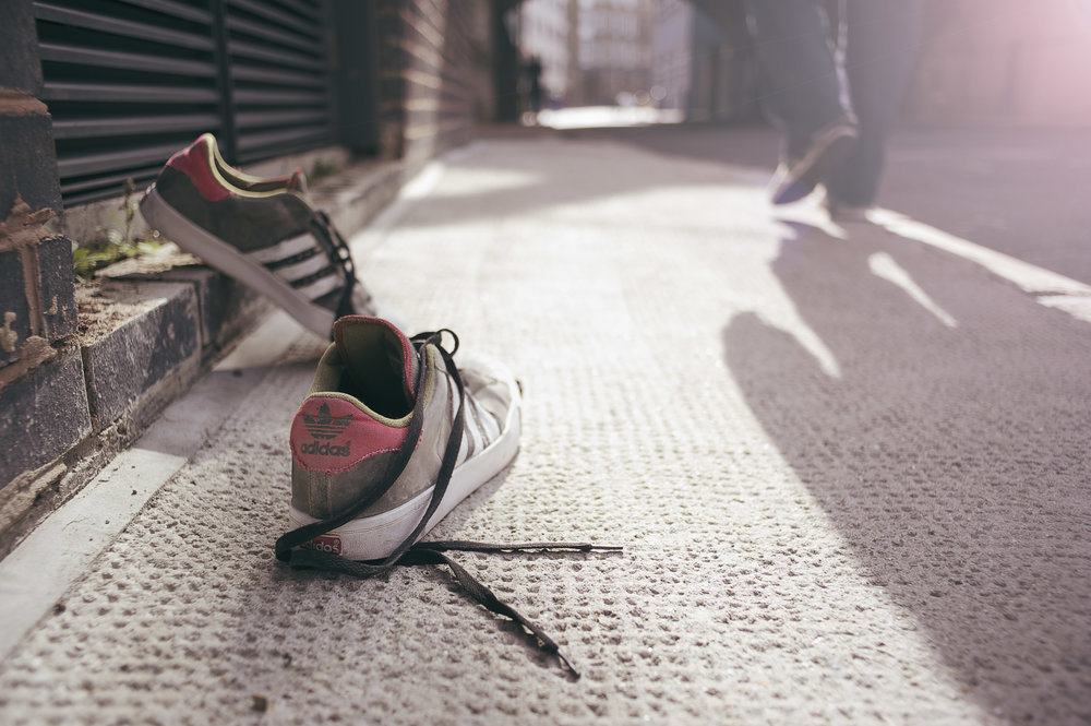 A mix of lifestyle and product photography of Adidas trainers on the street.