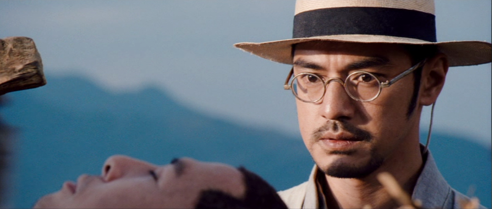 Takeshi Kaneshiro as Xu Baiju, overlooks an unconscious Liu Jinxi