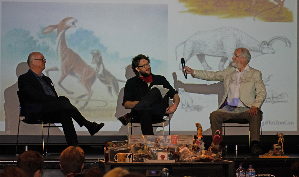 From left to right: Gert van Dijk, Darren Naish and Dougal Dixon on stage during the SpecBio discussion at TetZooCon 2018. Dougal Dixon illustrations relevant to (but not included within)  After Man  are on the screen behind us. Image: Georgia Witton-Maclean.