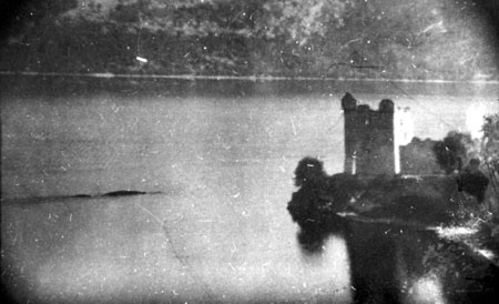 Peter Macnab's photo of 1955. This is the version lacking the vegetation in the foreground. Regarded by some Nessie proponents as depicting two monsters swimming in close proximity, it is most likely part of a boat wake, as suggested by the lines in the water about parallel to the 'monster(s)'. This is a scan of the original photo, provided by Dick Raynor (and available  here ). Image: (c) P. A. Macnab.