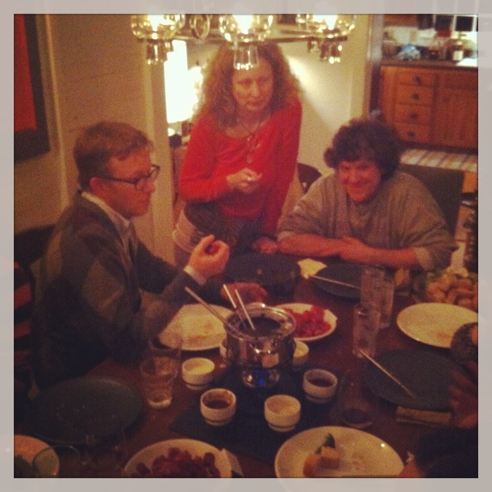 Party guests gathered around a pot of Beef Broth Fondue.
