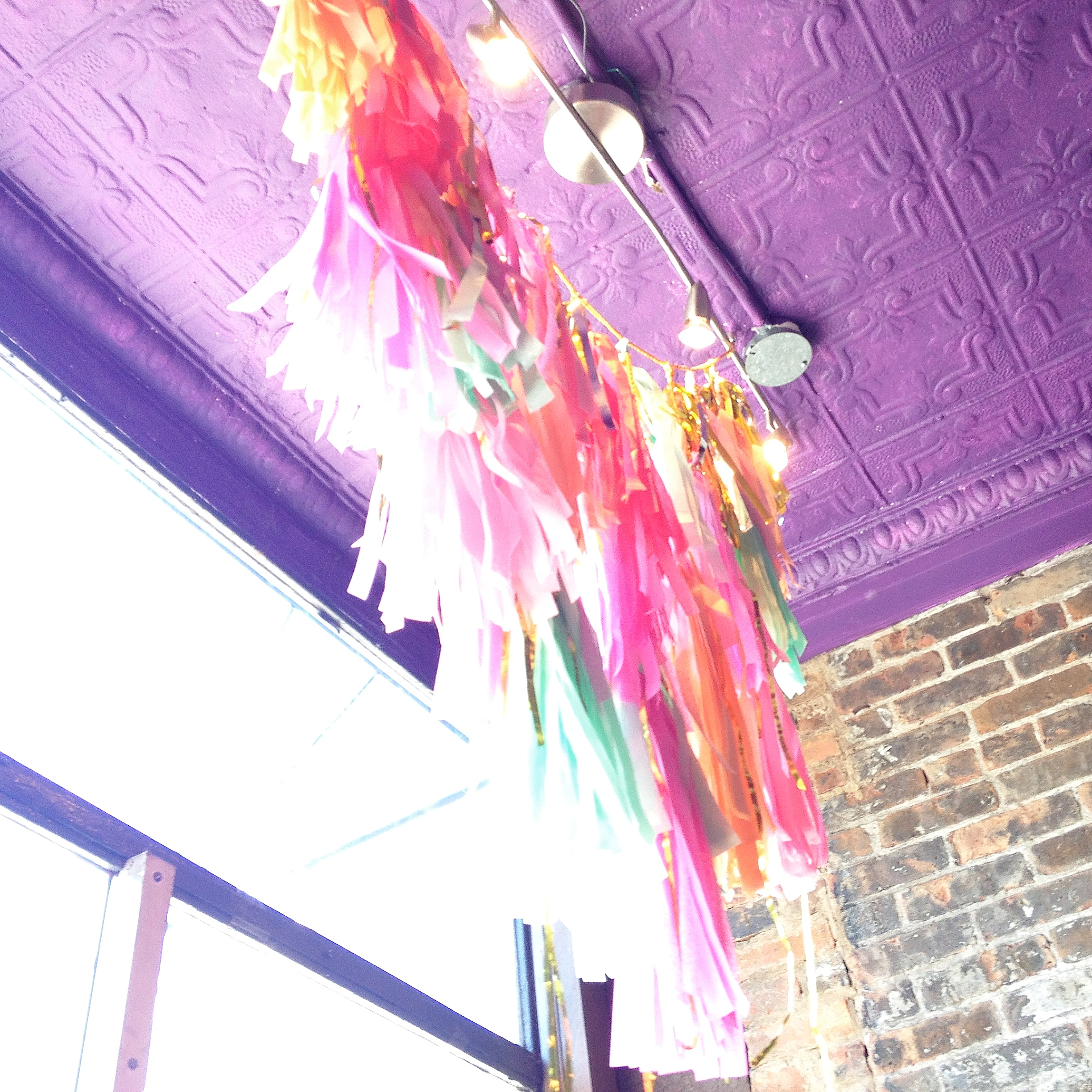 Tissue tassel garland window display by Sparkle Motion Decor
