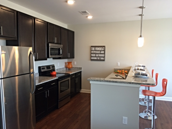 July 1, 2015 The kitchen in the model unit is decorated with pops of orange.