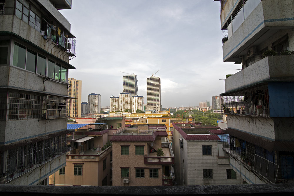 "The view from the apartment's balcony opens up to Guangzhou's continuously changing landscape. ""The government tore down the building we originally lived in and relocated us to these apartments. The view used to be of farm land for as far as you could see."" Mother reminensces."