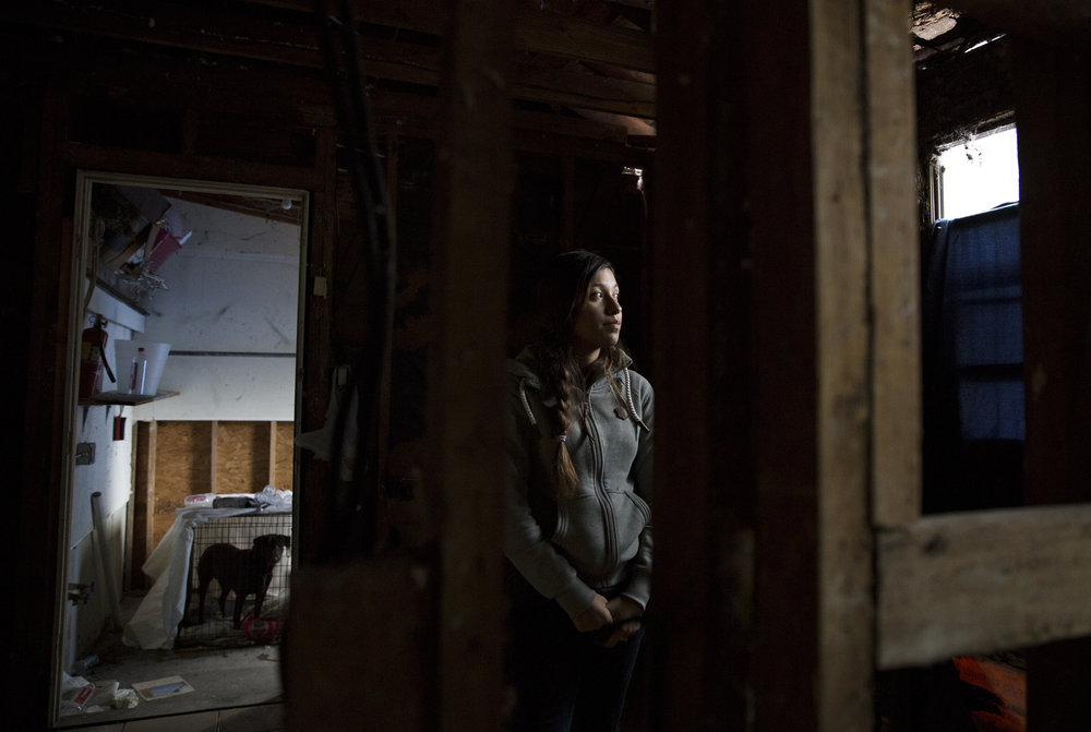 Anita Miranda, 24, stands in the kitchen where the roof first collapsed from Hurricane Harvey's rains. Unable to secure housing after Hurricane Harvey, the family returned to their storm-damaged home where rooms are gutted, utilities don't work and uncertainty about repairs continue to linger.