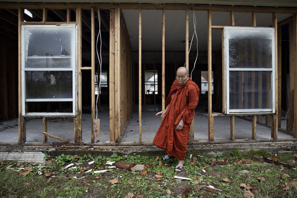 Venerable Sok Reas steps outside of Harvey-damaged monastery on Dec. 28, 2017. Though the Wat Buddha Raksmey temple has made some repairs to its buildings, the monastery for the monks remains gutted with questions of whether it will ever be rebuilt.