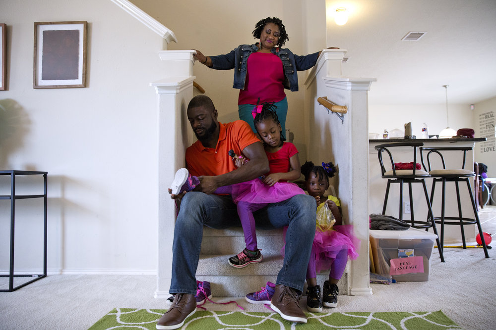 Syreeta Lazarus, 36, looks over her family while her husband, Tim Lazarus, helps his daughter put on her shoe in preparation for the park. Turner has suffered postpartum pre-eclampsia on three separate occasions after delivering her daughters.