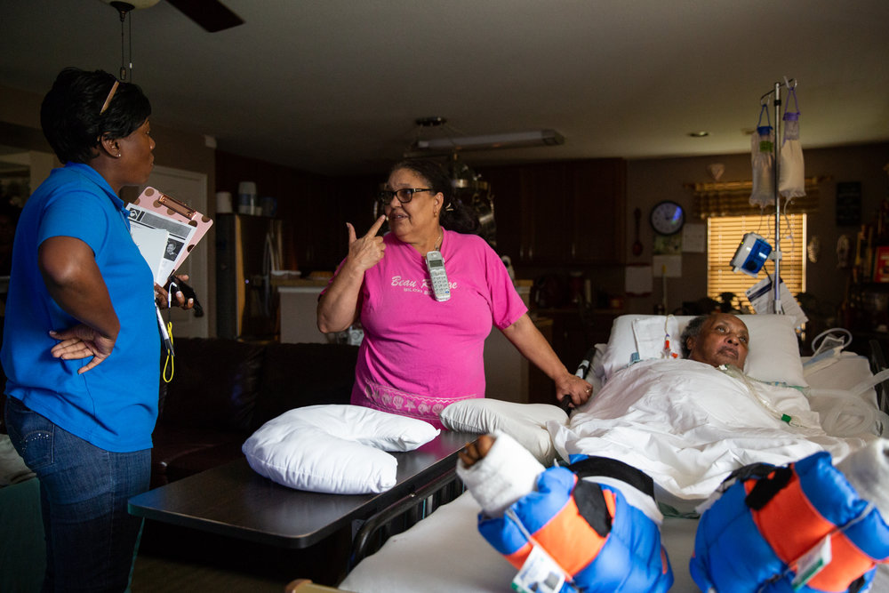 Charla Gilliam, left, talks with Lisa Bell, center, about the latest care update on David Haywood, right, during an in-home check up on June 20, 2018.