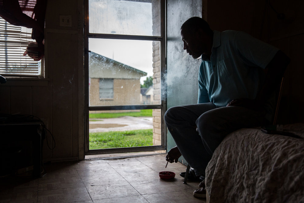 George James Jr., 51, smokes a cigarette in his living room that also serves as his current bedroom at his home in Houston. James, who is legally blind and on disability, feels left behind waiting for assistance to help repair his storm-damaged home.