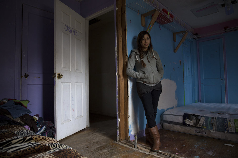 Anita Miranda, 24, stands in the family bedroom that suffered the least amount of structural damage on Thursday, December 14, 2017. The family is living in their flood-damaged house without power, running water or heat after Miranda said FEMA cut them off from its hotel assistance program for Hurricane Harvey victims.