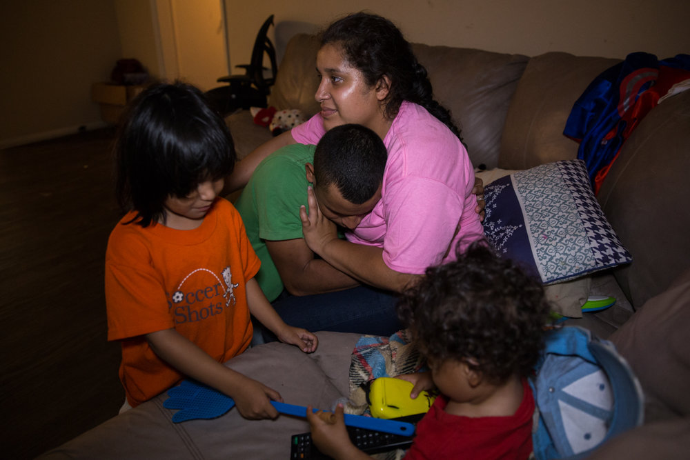 Karina Romero embraces her husband, Dikenis Carias, while their children Francois, 3, and Caleth, 1, play with each other on July 05, 2017. The family is reunited after being separated during the immigration process.