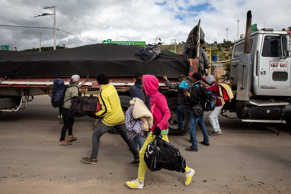 Venezuelan migrants rush to board a cargo truck that has offered them a ride farther down the highway to Bucaramanga, Colombia.