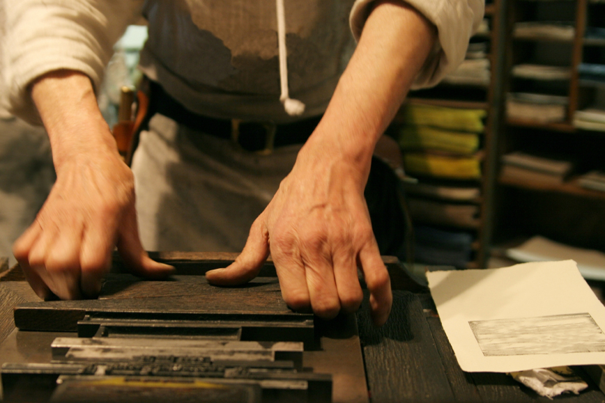 An artisan printer, specialising in letterpress printing, inserting moveable type into a frame.