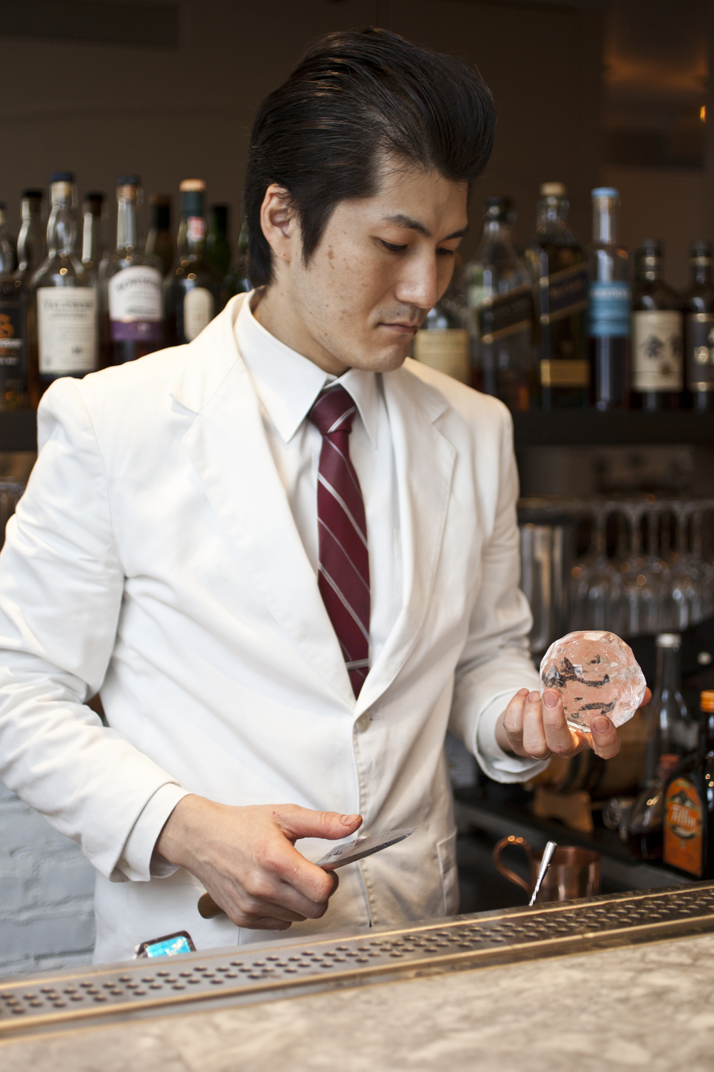 Bartender Shinya Yamao carving ice for cocktails at Piora