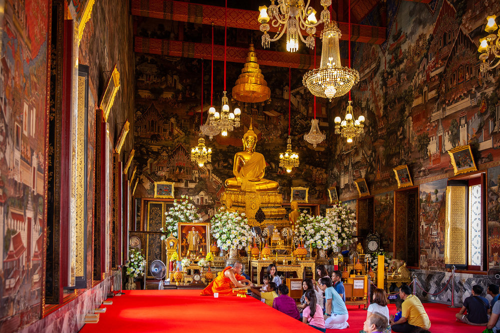 a monk gives blessings inside a chapel at Wat Arun