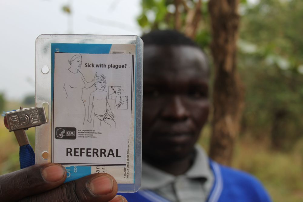 Traditional healer Mark Wadribo shows off his plague referral card
