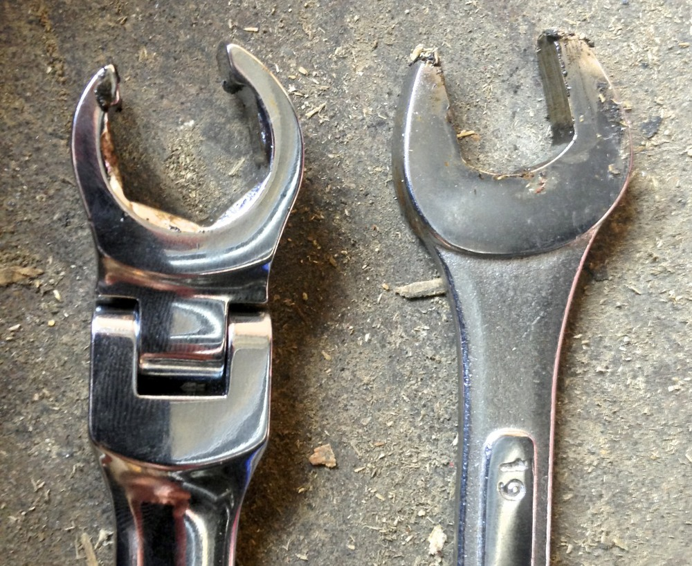 "Flare (left) and open (right) wrenches.  The ""teeth"" on the end of flare wrench fit around the back of the bolt for a better grip."